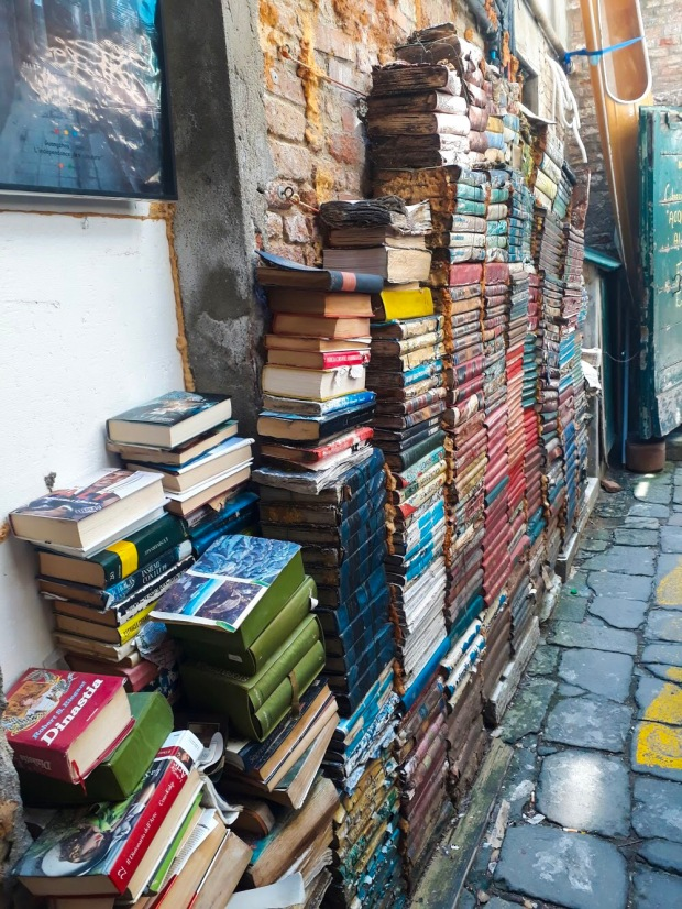 Books stacked high in Acqua Altra Liberia, Venice, Italy
