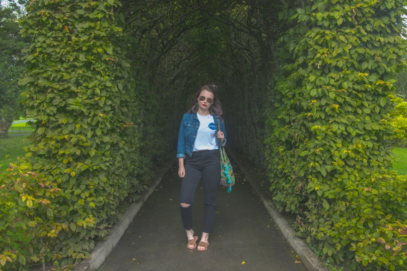 Fashion blogger poses in vine arch, in suede sliders, black ripped jeans, NASA tee and denim jacket